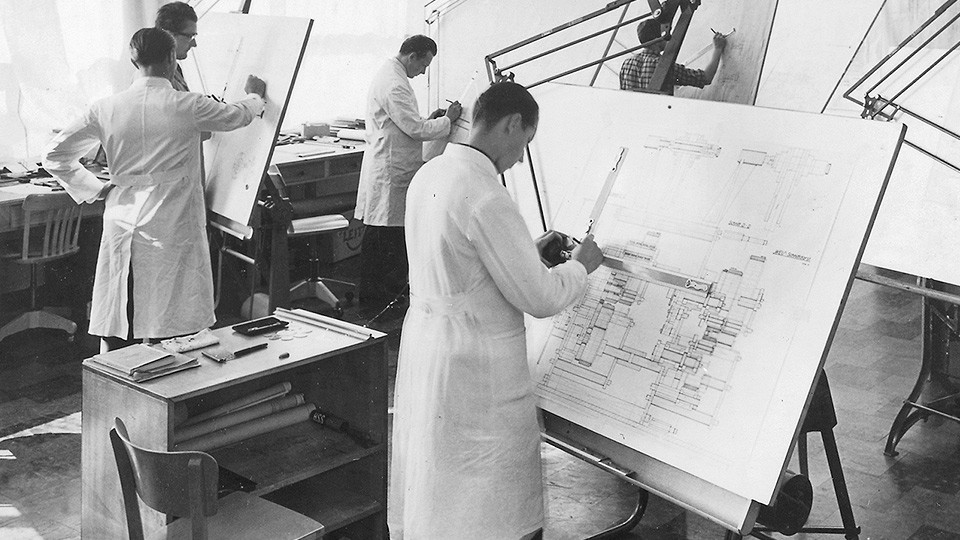 Black and white picture of people drawing plans